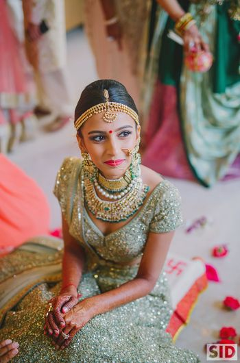 Bride earing polki jewellery and sparkly lehenga