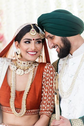 Bridal portrait with layered jewellery and happy groom