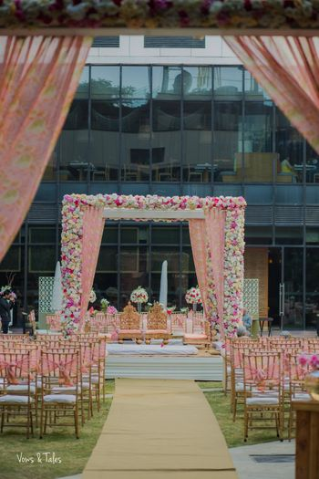 Photo of Floral drapes and light pink mandap with chairs