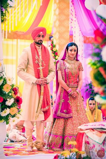 Photo of Bride in Pink Lehenga and Groom in Pink Pagdi