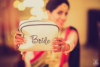 Photo of Bride getting ready with customised makeup bag