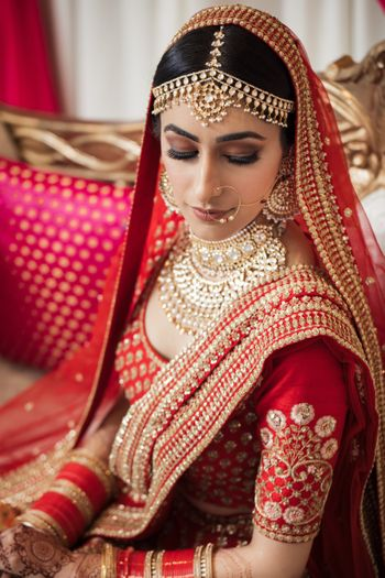 Photo of Close up shot of a bride wearing a red Sabyasachi lehenga on her wedding.