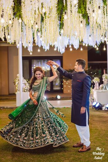 Bride twirling in dark green lehenga with groom