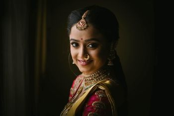 Happy bridal posing in beautiful gold jewellery.