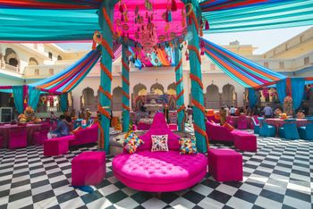 A colorful mehendi setup with tents, marigolds and dreamcatchers