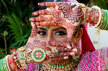 Photo of Bride posing showing off her bridal mehendi and haathphool