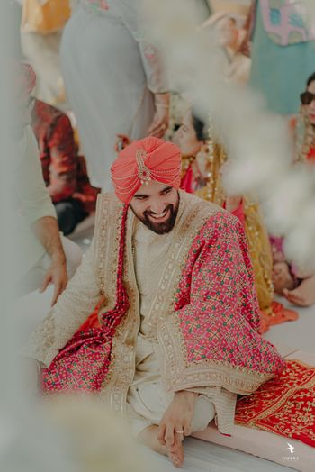 Photo of The groom in a beige sherwani, and a bright pink dupatta