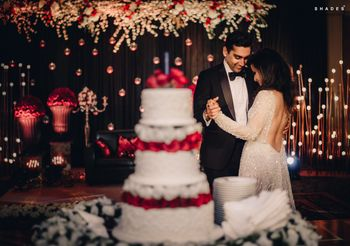 A couple dancing infront of a 3-tier cake on their reception
