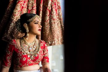 Photo of Getting ready bridal portrait with lehenga in backdrop