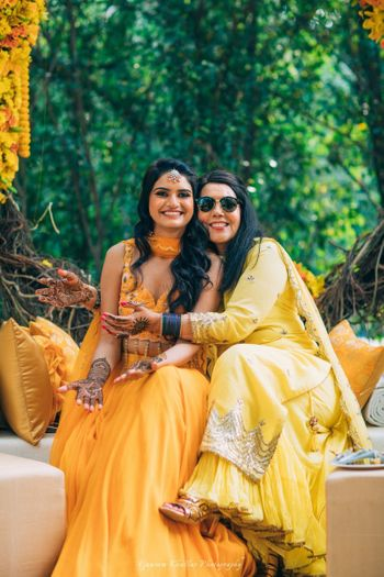 Photo of Bride with sister wearing yellow mehendi outfit