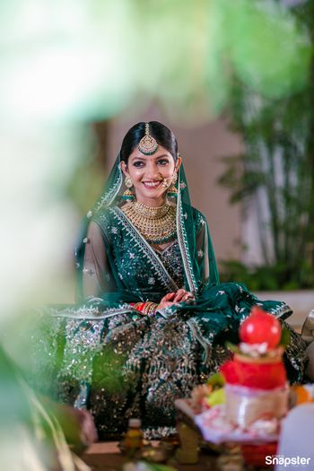 Photo of A bride in a green lehenga and oversized mangtikka on her wedding day