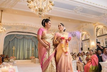Photo of bride in light pink kanjivaram entering with her mom
