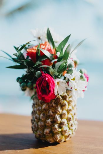 Photo of Tropical theme centrepiece with pineapple and flowers