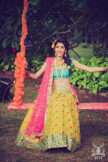Photo of bright colorblocked lehenga in leheriya yellow pink and blue with mirror work detailing
