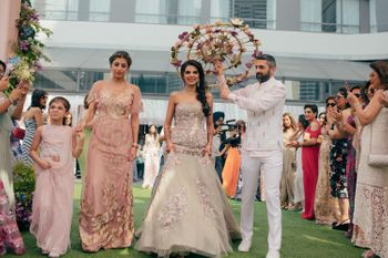 Photo of Bride entering mehendi with brother holding floral umbrella