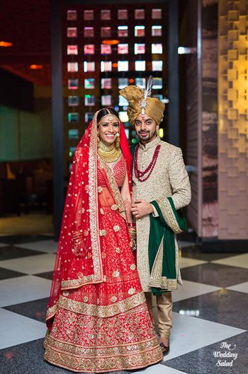 Red bridal lehenga with the groom in emerald