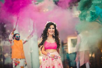 A bride in a pink outfit entering with smoke bombs for her mehndi ceremony