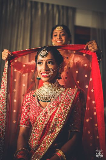 Photo of Bride with sister placing lehenga on head shot