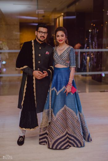 A bride and groom pose on their sangeet nigh