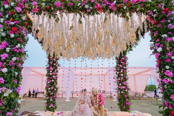 Photo of The bride and groom under a gorgeous floral mandap.