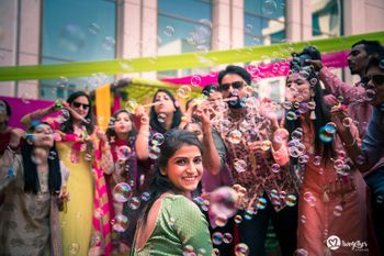 Cute mehendi photo of bride with bridesmaids blowing bubbles