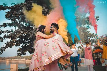 A groom lifting a bride for their mehndi entry, amidst smoke bombs