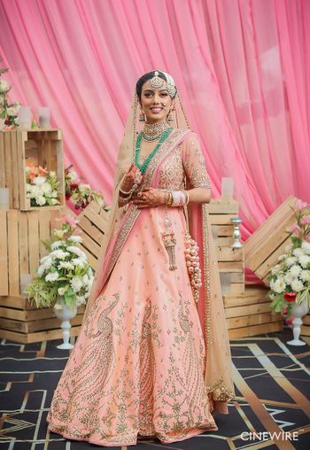 Sikh bride with peach lehenga and green jewellery