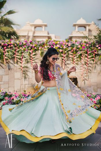 Photo of Bride twirling in blue mehendi lehenga