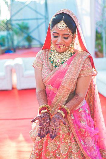 Fuschia pink bridal lehenga with emerald necklace