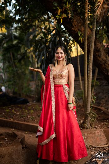 A bride to be in a red and gold lehenga for her mehndi