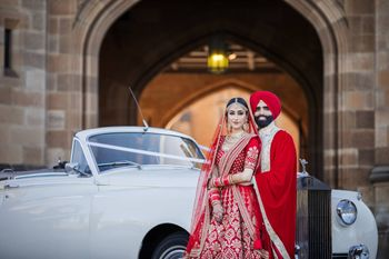 Photo of A color-coordinated couple posing on their wedding day in front of vintage car.