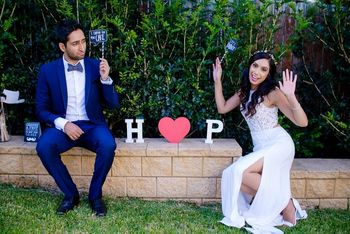 Photo of unique couple protrait against their own initials with whacky poses