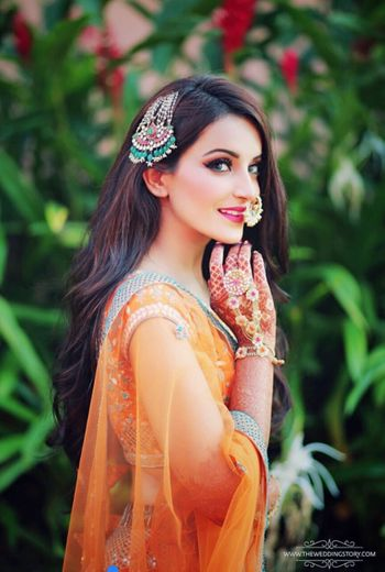 Floral hand jewellery and jhoomer for mehendi with orange lehenga