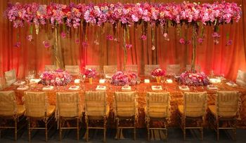 Pink and gold theme table setting with floral canopy