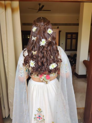 Half tied hair with a crown braid and floral adornments.