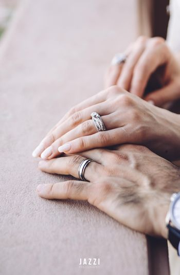 His and her hands with engagement rings