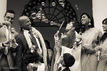 Bride blowing bubbles on groom