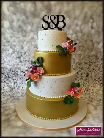 Photo of Gold and white 4 tier wedding cake with monogram topper
