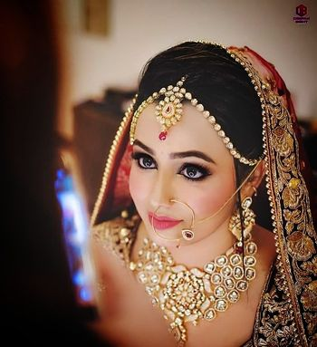 A bride with peach and gold jewelry poses for the camera.