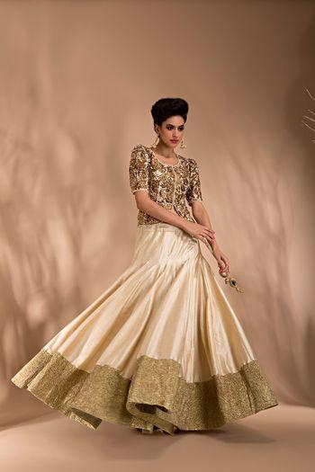 Photo of gold lehenga with long blouse