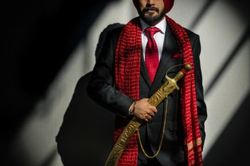 Photo of a groom wearing a black tuxedo with a red stole, a red tie and a red turban
