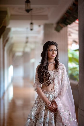 Long wavy hair and subtle makeup with pastel lehenga