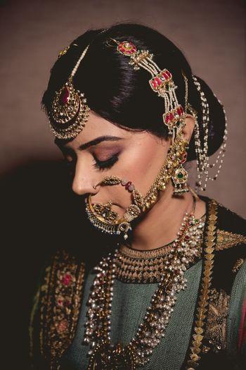 A bride with heavy jewelry, mangtikka an nath. d