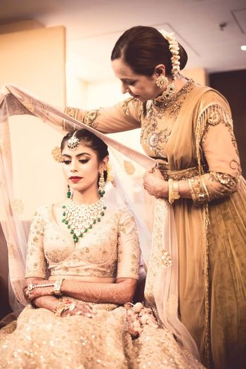 Pretty mom placing dupatta on bride for wedding