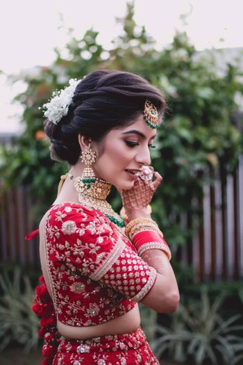 Photo of Bridal shot wearing jewellery in red lehenga