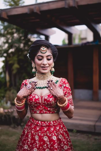 Bride in red blouse and green jewellery