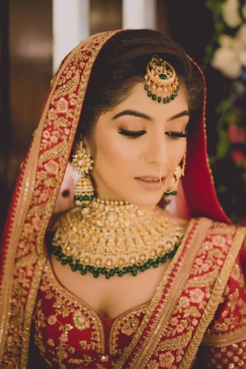 Photo of Bride in red lehenga green jewellery