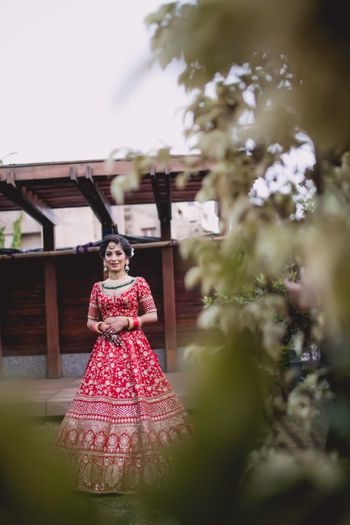 Photo of Bride in red embellished lehenga long shot