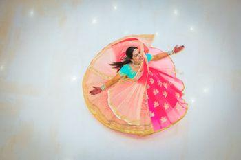 Top shot of bride twirling in pink and aqua lehenga