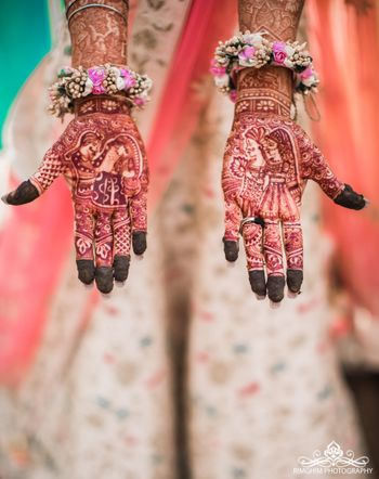 Mehendi hands with portraits and floral hand jewellery